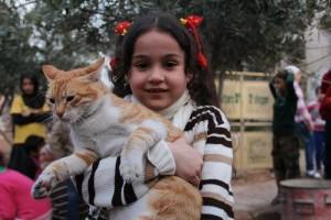 Ernesto in braccio ad una bambina ad Aleppo - Foto di Mohammad Alaa Aljaleel